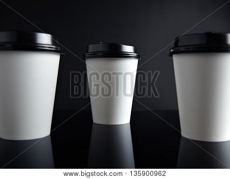 Close view white take away paper cups for hot beverages closed with caps presented in perspective, isolated on black and mirrored. Retail mockup presentation