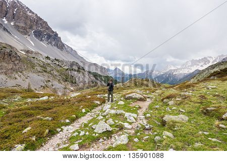 Hiker photographing landscape on the mountains with dramatic sky and storm clouds. Summer adventures and exploration on the Alps.