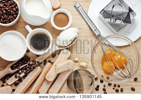 Cooking tiramisu concept ingredients for making italian dessert on wooden table process of preparation traditional cake top view