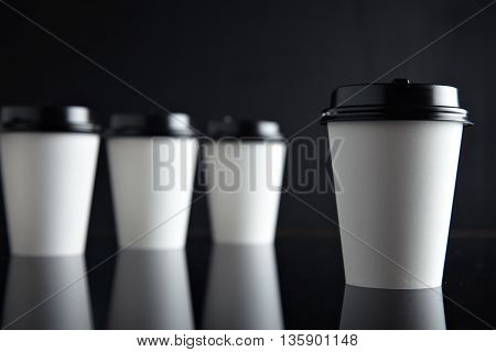 Retail mockup presentation, White take away cardboard paper cups closed with caps isolated on black and mirrored. One cup presented in front