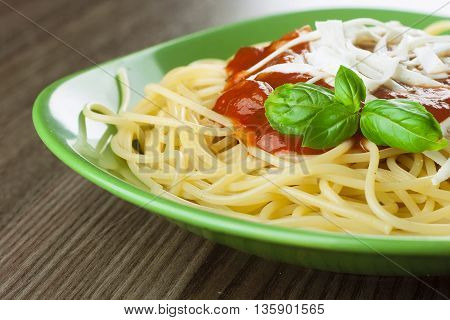 Cooked spaghetti with traditional italian tomato sauce served in a green plate on a wooden table