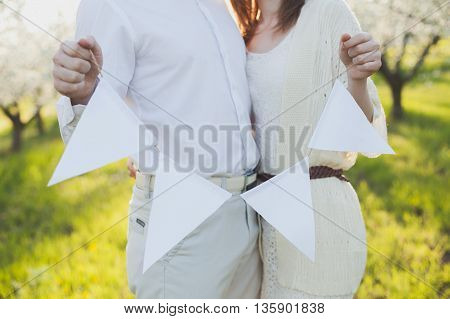 the man and woman standing together. hands of the man and the woman the holding tags on a thread. tags on a thread.
