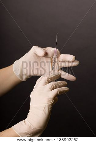 Female hands in latex gloves. Flicking syringe. Doctor or nurse preparing for medical procedure. Dark background