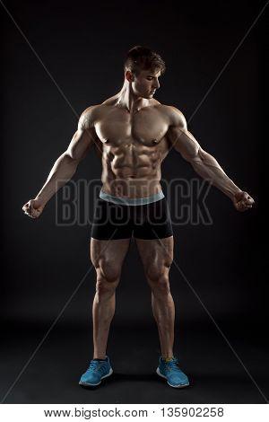 Muscular bodybuilder guy doing posing over black background. Naked torso in shorts. full height