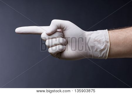 Male hand in latex glove. Doctor or nurse poiting with a finger. Dark background
