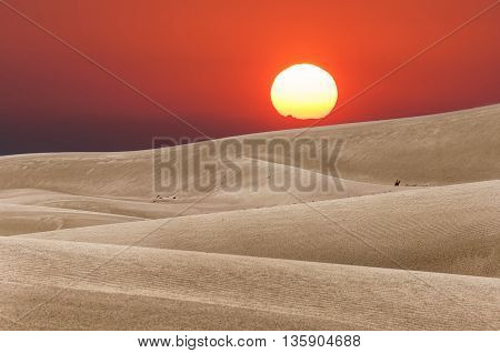 Red sunset in the desert. Sun hiding behind the sand dunes