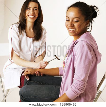 young smiling doctor examine patient, measuring pressure to smiling afro american woman, happy lifestyle real people