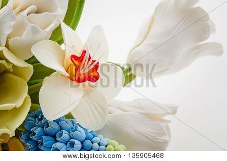 Beautiful handmade art clay spring flower bouquet. Bridal accessory. Over white background. Close-up.
