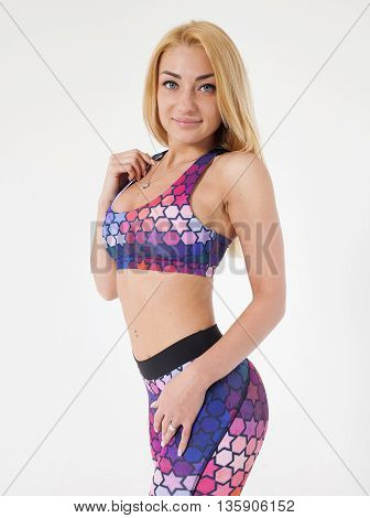 Attractive fit woman exercising in studio . Image of healthy young female athlete doing fitness workout against white background.