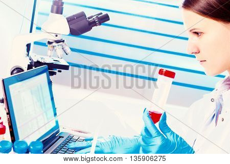 Portrait of pretty girl laboratory assistant analyzing a blood sample at hospital laboratory with laptop  pc. Toned image