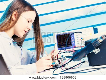 Girl repairing electronic device on the circuit board. Toned image