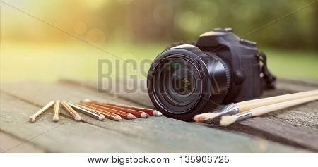 Camera with pencil and brush - photography design art concept