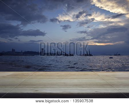 Empty wooden table in front of construction crane at sea and city for your product display montage