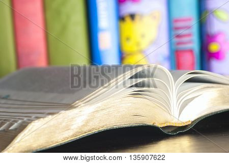 Set of books in the library. Knowledge, Science. Open book, stack of colorful hardback books on light table. Back to school. Copy space for text. Toned image.