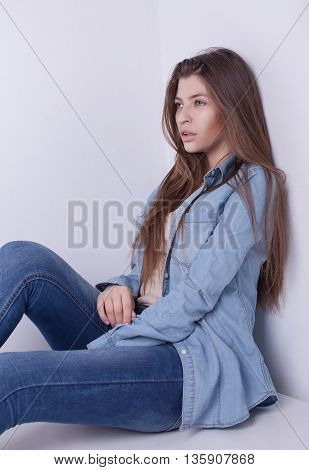 Young European attractive sexy fashion model with long blond natural hair, beautiful eyes, full lips, perfect skin is posing in jeans and shirt in studio for glamour vogue test photo shoot