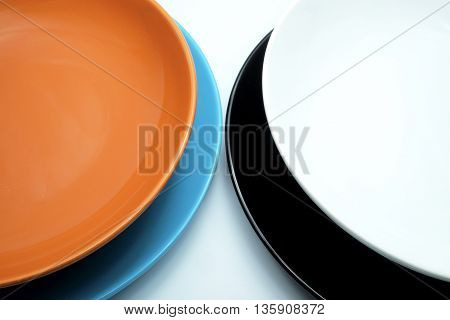 Colorful ceramic plates for the main dishes on blue-white background.