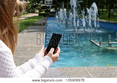 Girl holding the phone close-up of hands in a park near the fountain. Shallow depth of field