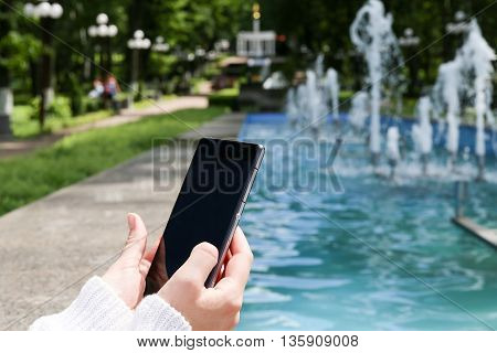 Closeup of female hand using a smart phone in a park near the fountain. Shallow depth of field