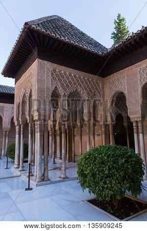 Beautiful Moorish arches in main courtyard of the Nasrid dynasty Palace of the Lions in fortress complex Alhambra in Granada. Spain