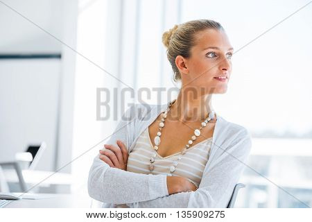 Attractive young woman sitting at desk and looking away