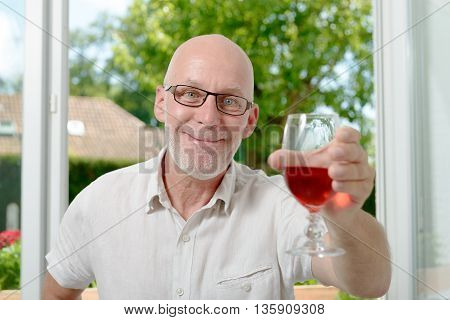 a middle-aged man drinking a glass of wine