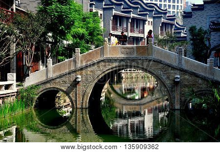 Chengdu China - October 7 2010: A serene three arched bridge spans one of the waterways at Long Tan Water Town