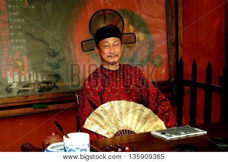 Chengdu China - November 4 2007: Actor dressed in traditional Mandarin robe with fan does Chinese caligraphy in his booth on historic Jin Li Street