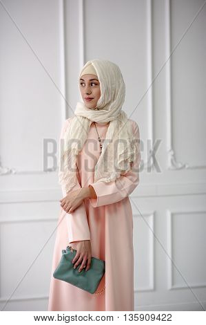 East girl in a beautiful bright Muslim dress, a shawl on her head on a light classical background