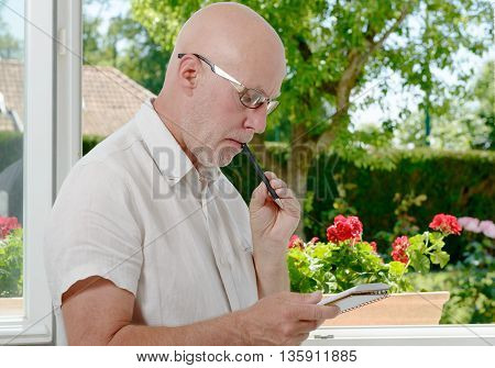 a mature man near a window taking notes