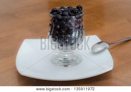 Frozen black currant in the glass with drops of water