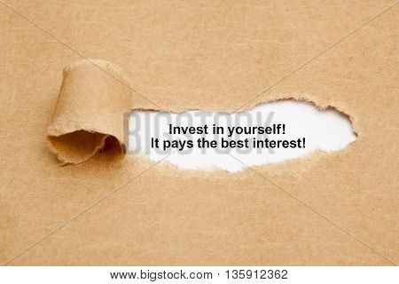 The quote Invest in yourself it pays the best interest appearing behind ripped brown paper.