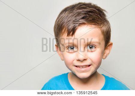 Child in joy smilling at camera on white background