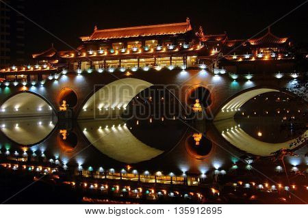 Chengdu China - September 18 2006: The Long Qiao covered bridge at night reflected in the still waters of the Funan River