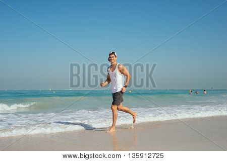Handsome sports man jogging on the beach.