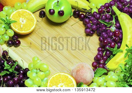 Healthy summer fruit variety.Sweet cherries,bananas,yellow and red grapes,peach,oranges,apple and mint on wooden board in center.Top view,copy space