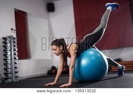 Attractive girl training on a ball in the gym.