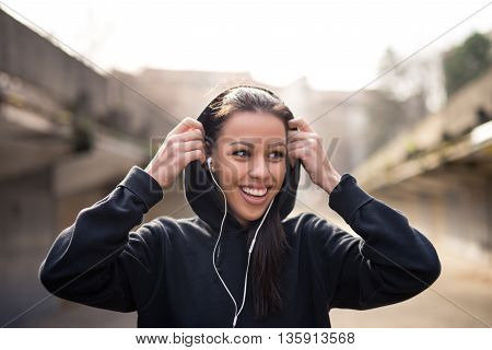 Attractive girl putting the hood on and preparing for the fitness.