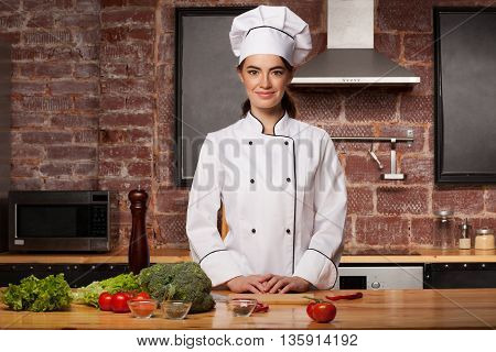 Female Cook In A White Hat In The Kitchen