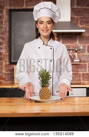 Woman Chef Cook With Pineapple On The Plate In Kitchen