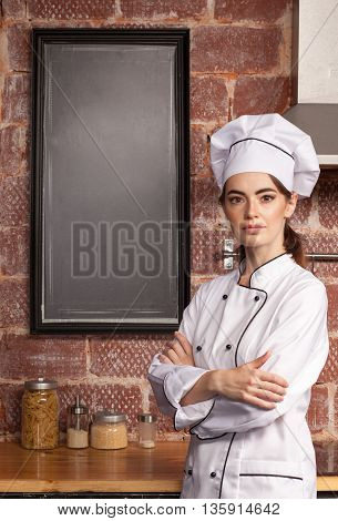 Female Cook Standing In Kitchen Near Blank Chalk Board