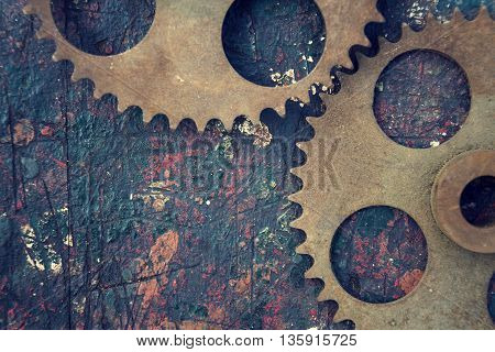 Filtered Picture Of Cogwheels On A Colorful Wooden Background