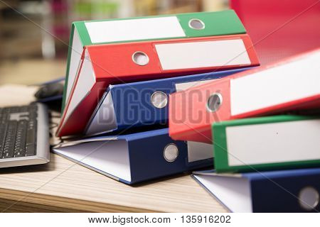 Stacks of office binders on desk