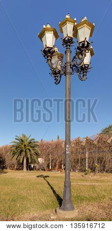 old lantern in a park with palm trees