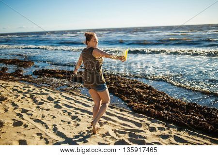 Girl spits orange juice and sprays it on wind. Concept of freedom, relax, happiness
