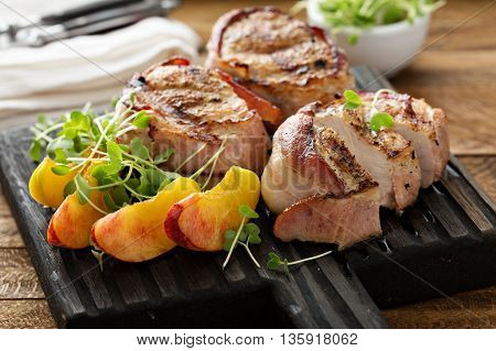 Grilled turkey tenderloins wrapped with bacon served with fresh peaches