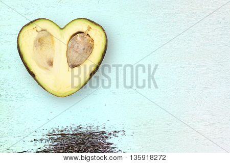 avocado in the shape of a heart on a rustic wood green table