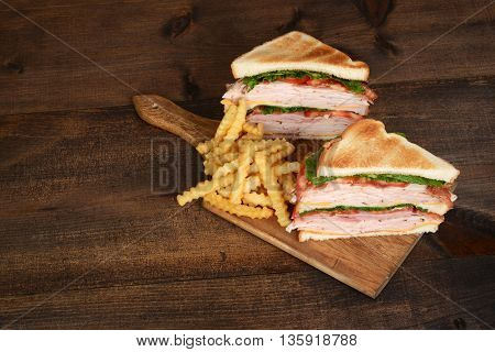 top view toasted chicken club sandwich on cutting board