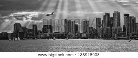 TORONTO SKYLINE IN BLACK AND WHITE WITH SUNBEAMS PROTRUDING THROUGH CLOUDS AND AIRPLANE IN THE DISTANCE