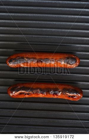 two sausages on a black indoor grill