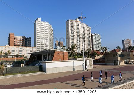 DURBAN SOUTH AFRICA - JUNE 24 2016: Seven unknown morning joggers on beach front paved promenade against Golden Mile city skyline in Durban South Africa